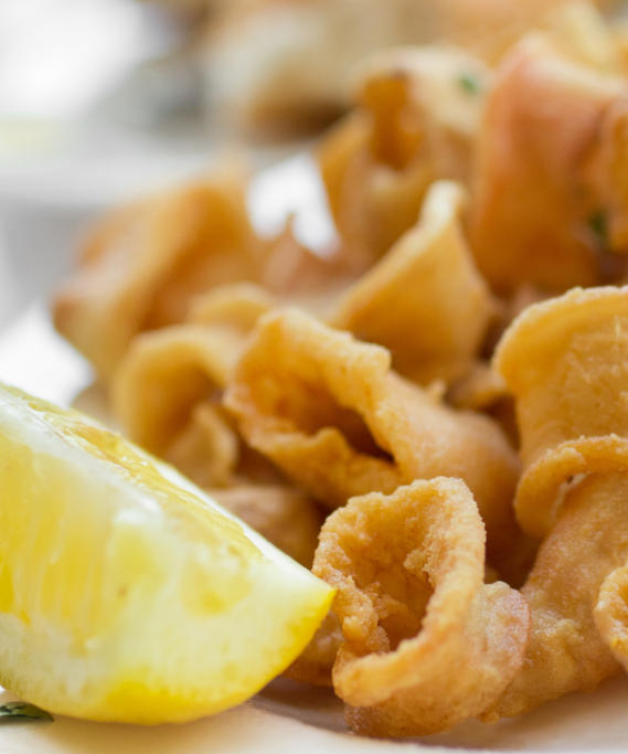 Traditional Italian style fried calamari with a wedge of lemon on the side