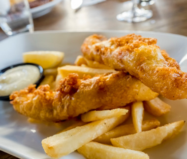 Battered fish and chips (fries) freshly cooked to golden brown, served on a plate with a wedge of lemon and some sauce.
