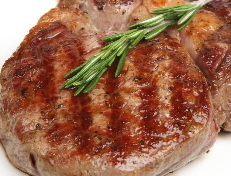 Juicy rib-eye beef steak with rosemary.